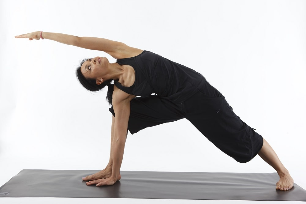 A female yoga practitioner doing Revolved Side Angle Pose as part of her plan to improve her yoga asanas.
