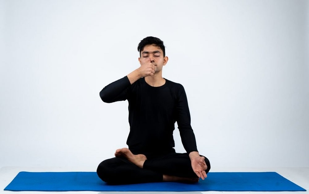 A male yoga practitioner doing alternate nostril breathing to improve his pranayama practice.