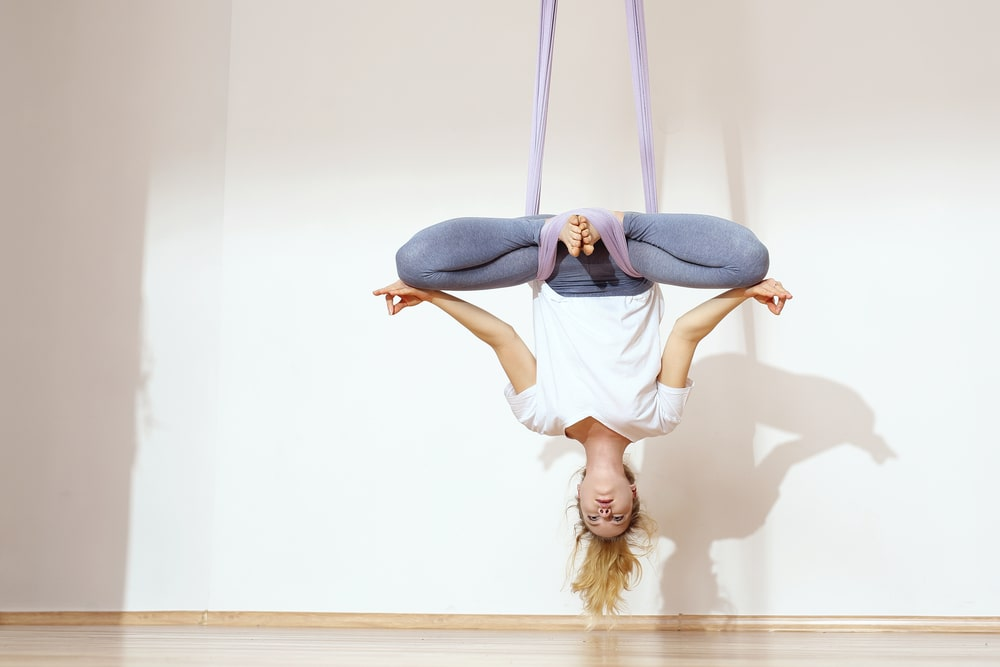 A female yoga instructor suspended upside down from a yoga swing, getting her teacher training certification in aerial yoga at an indoor studio.