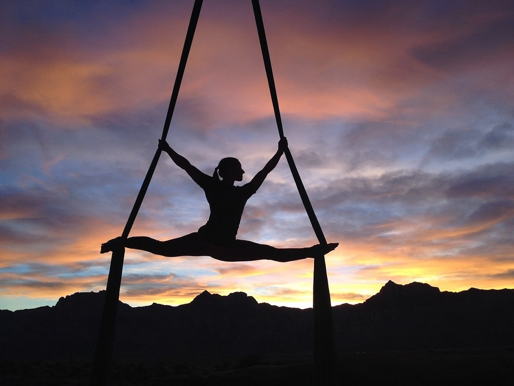 A female yoga instructor getting her aerial yoga teacher training during a class held outdoors.