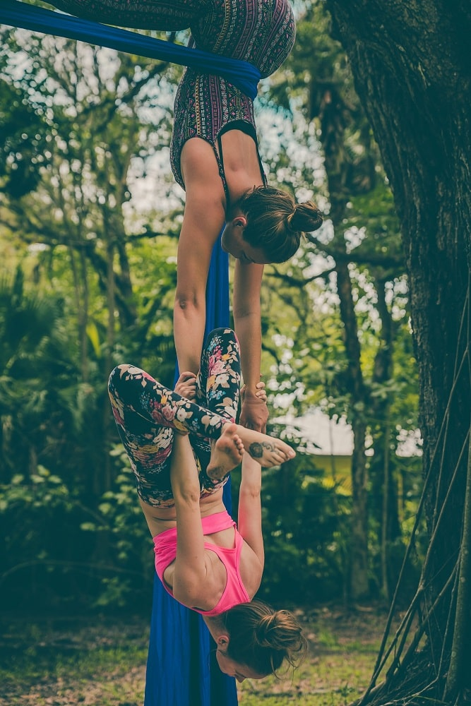 An aerial yoga teacher suspended from a tree, helping her student achieve the proper pose.