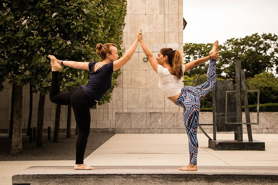 Two women wearing snug, high-quality leggings, practicing their yoga routine together at an outdoor location.