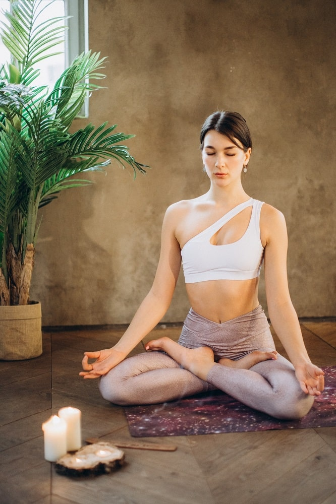 A woman doing Lotus Pose while meditating on her yoga mat, wearing light-colored leggings with the perfect and comfortable fit.