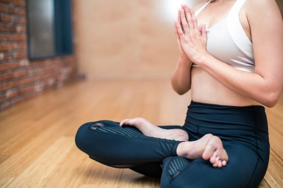 A woman doing Lotus Pose with praying hands, wearing a pair of well-fitting yoga leggings.