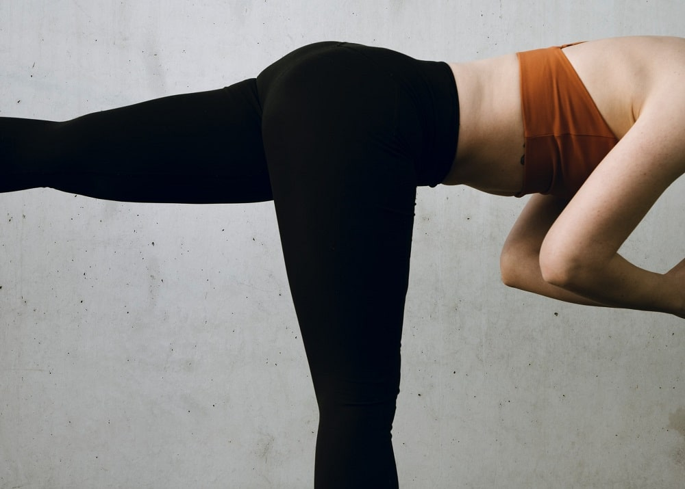 A woman practicing yoga while wearing a comfortable pair of black yoga leggings that fit her well.
