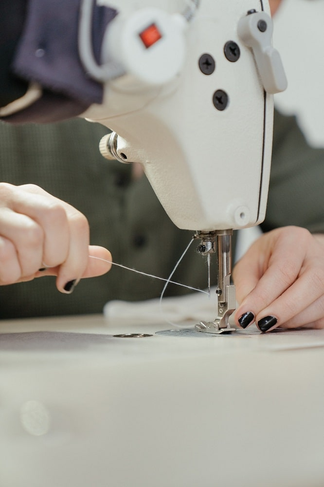 A woman repairing her loose-fitting yoga pants using a sewing machine.