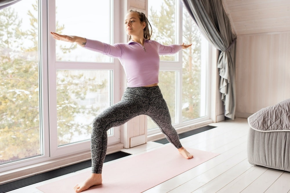 A woman doing her morning yoga routine in her bedroom, wearing perfectly shrunk yoga leggings that her well.