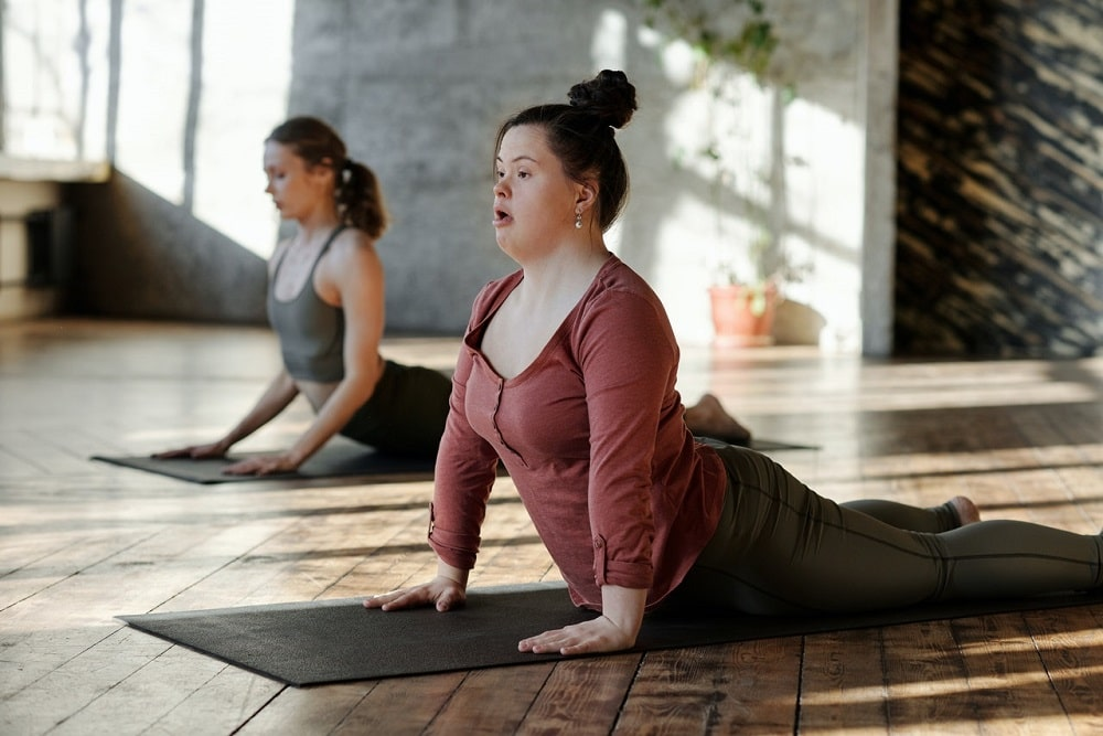 A woman doing Cobra Pose with a friend, wearing tight-fitting yoga leggings made of spandex material.