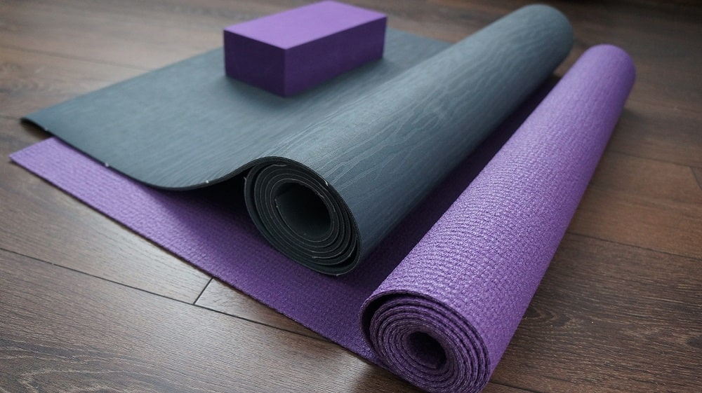 Blue and purple yoga mats and a purple yoga block laid on the floor.