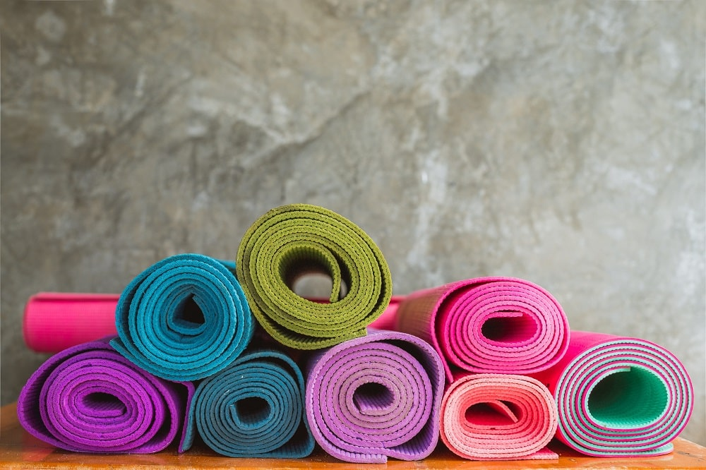Yoga mats of various colors rolled and stacked neatly on a wooden surface.