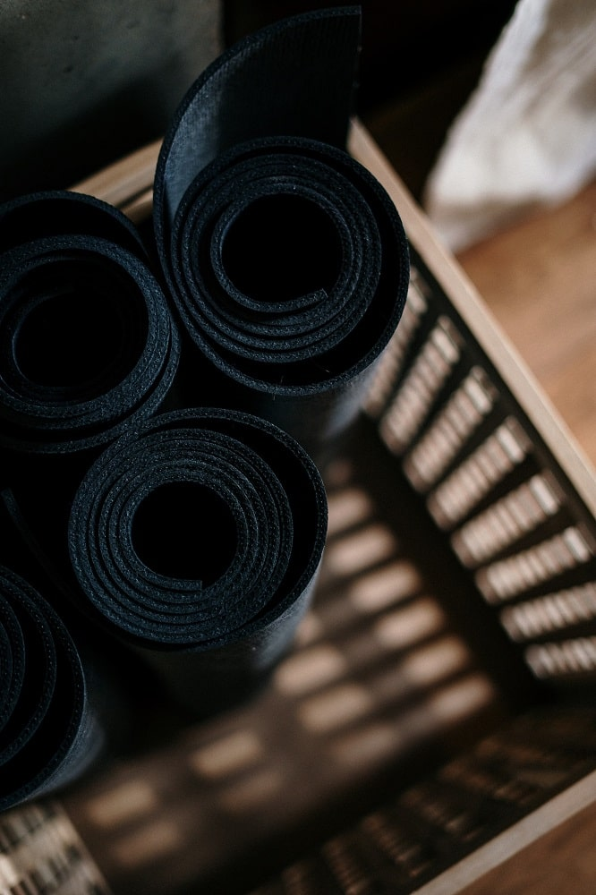 Yoga mats rolled and tucked away neatly in a storage bin.