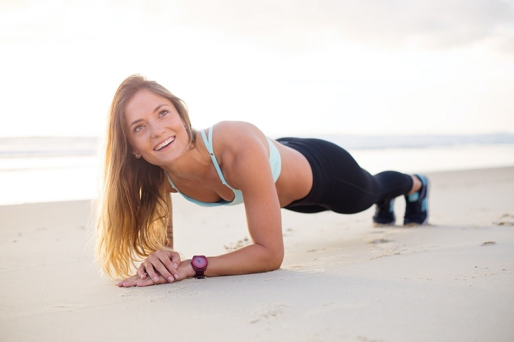 A smiling woman with a perfect set of teeth, doing Plank Pose on the beach.