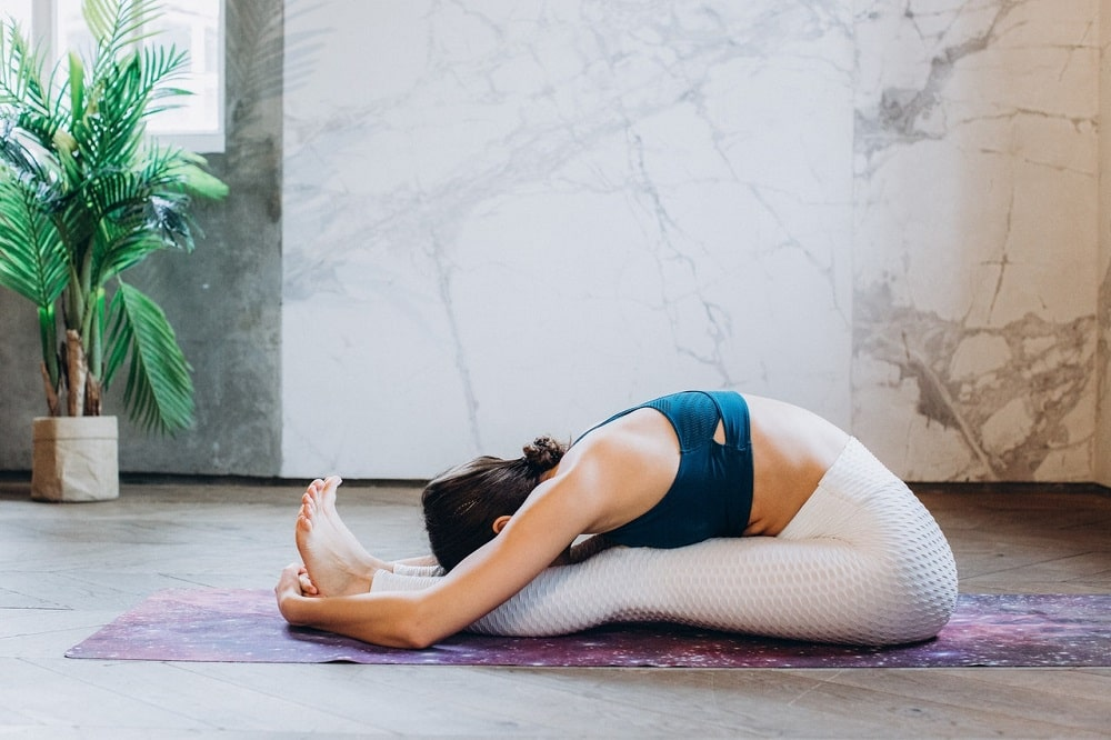 A female yogi doing Paschimottanasana or Seated Forward Bend to increase saliva production and improve overall oral health.