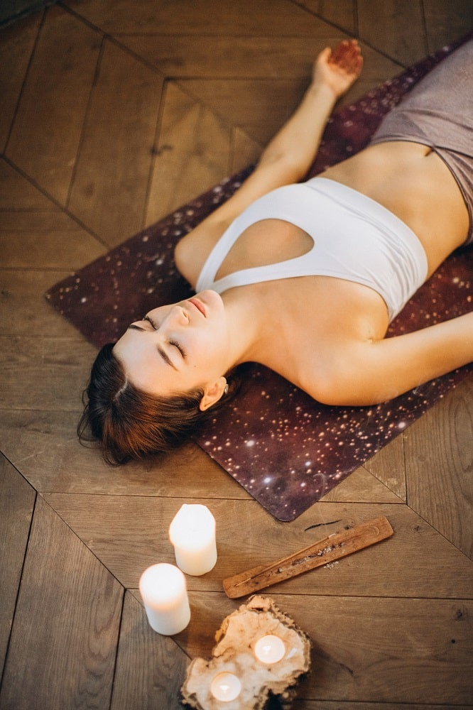 A woman practicing effortless relaxation during her yoga nidra session, with candles to promote a relaxing mood.