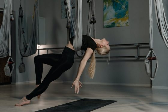 A woman doing aerial yoga using a yoga swing attached to the ceiling at an indoor studio.