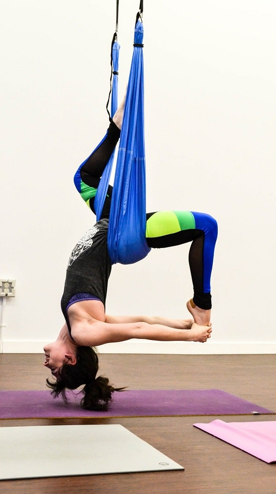 A woman demonstrating flexibility with the use of a yoga swing inside an indoor yoga studio.