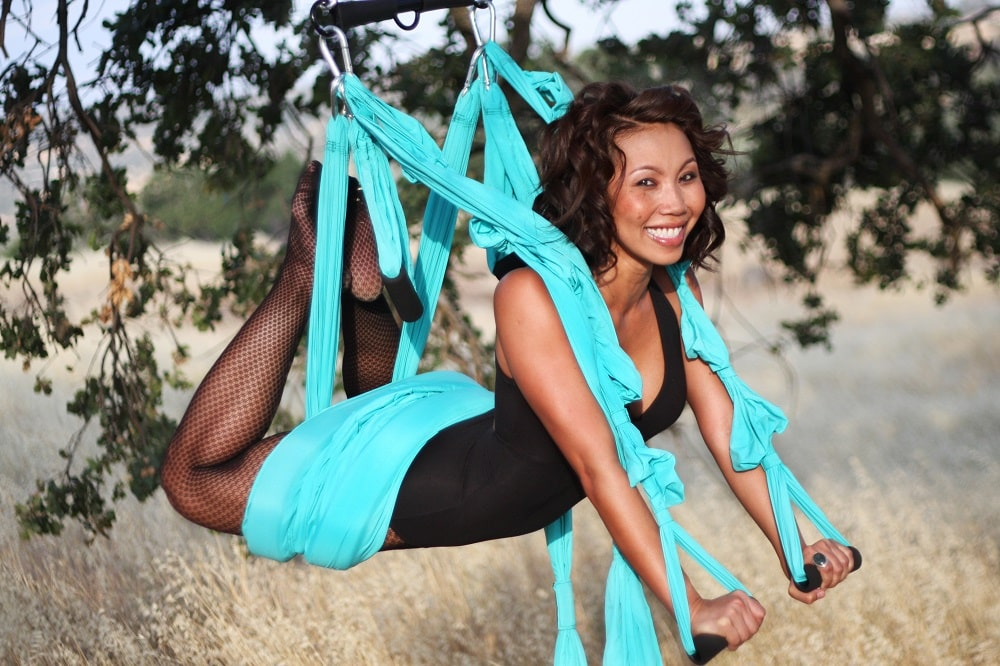 A woman doing yoga on a swing mounted to a tree outdoors for her yoga session.
