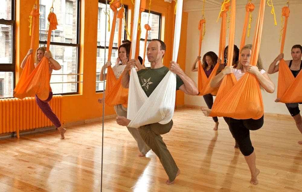 A male yoga instructor leading his students during an aerial yoga session.