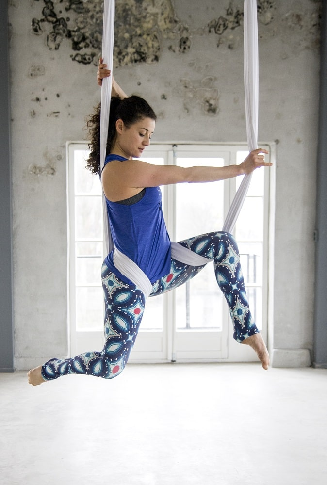 A female yogi using a yoga swing to demonstrate a basic pose for her indoor aerial yoga session.