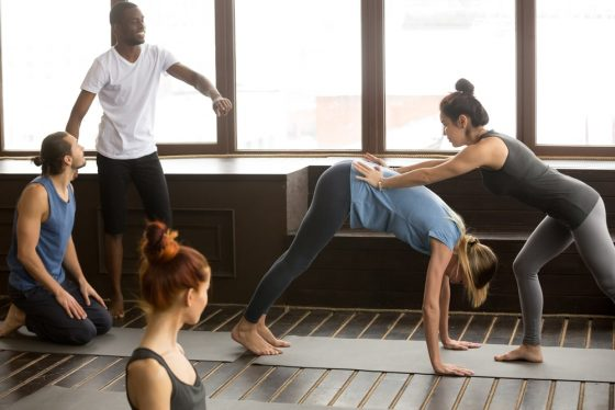 A yoga instructor assisting one of her students to achieve the proper form for Downward-Facing Dog, with the rest of the students watching during a yoga class.