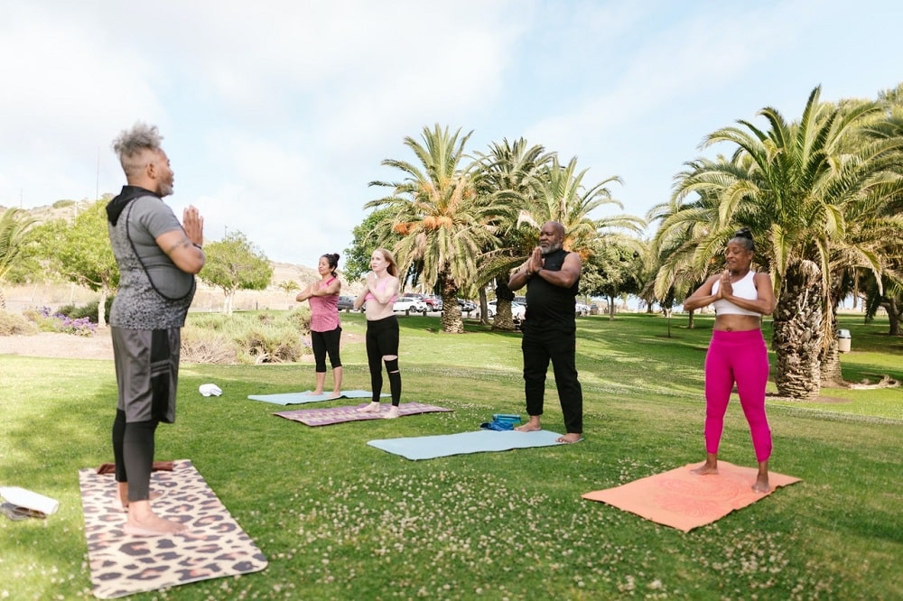 An uncertified yoga teacher standing with praying hands, guiding the class during an outdoor yoga session.