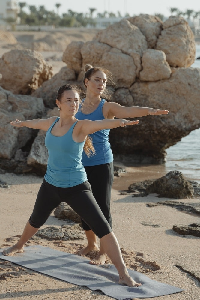 A yoga instructor and member of the Yoga Alliance, guiding one her students with Warrior Pose 2 during a yoga class at a seaside location.