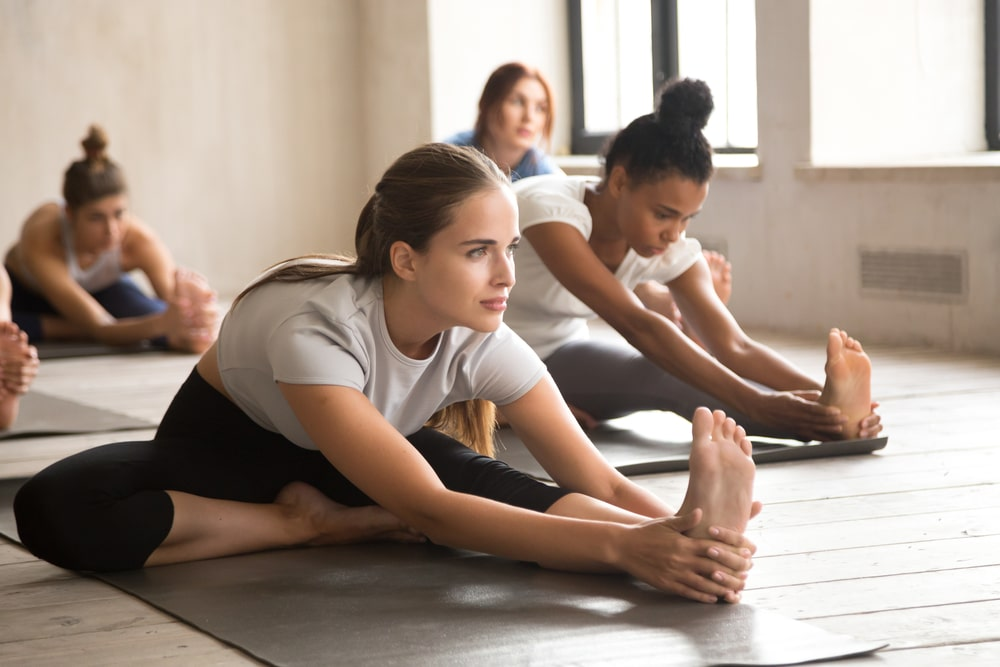 A female yoga instructor guiding her students with their stretching exercises during an indoor yoga session.