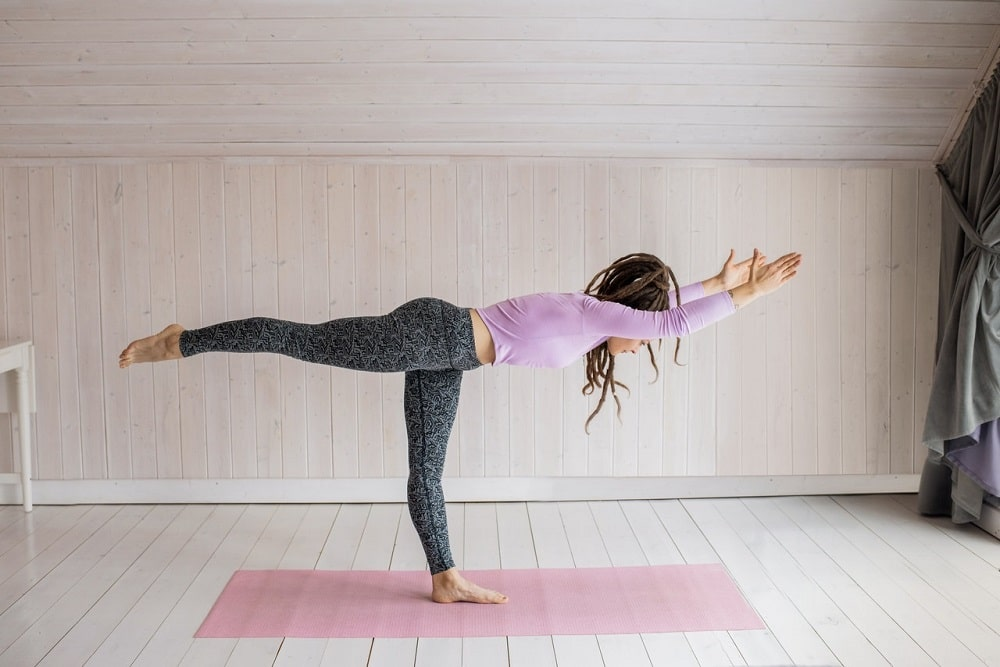 A woman enjoying the fitness benefits of yoga while doing Warrior 3 pose on a pink yoga mat.