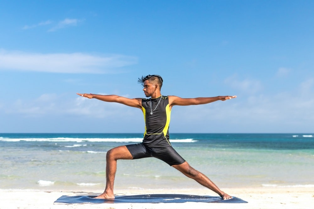 A man doing Warrior Pose 2 at the beach, demonstrating static balance by maintaining proper form.