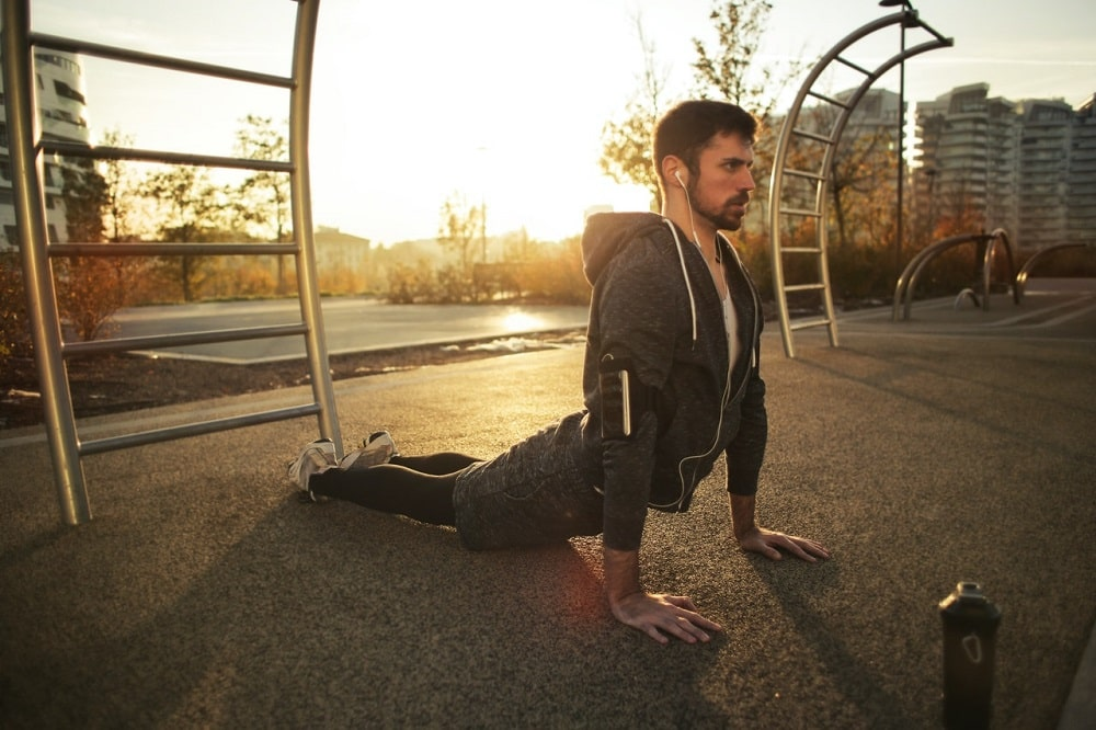 A man doing Sphinx Pose in the park for his yoga routine that helps strengthen the muscles.