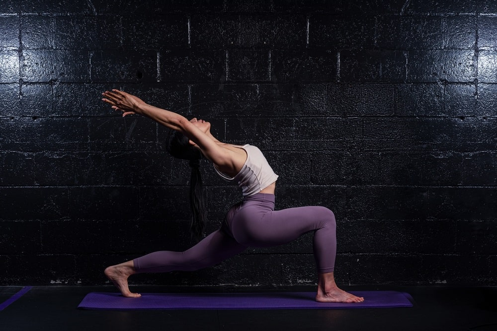 A female yogi doing Warrior I Pose as part of her Vin Yin Yoga routine indoors.