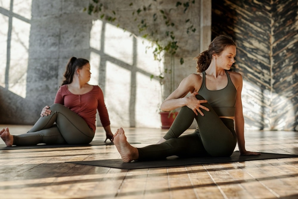 A couple of women doing yoga together barefooted.