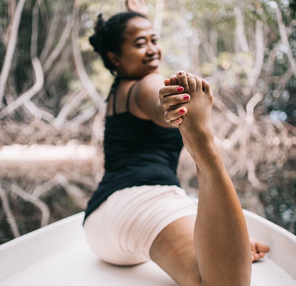 A close look at a woman doing yoga poses while on the bow of a boat on barefoot.