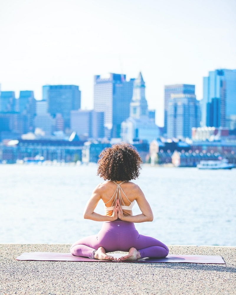 A female yogi practicing her outdoor yoga kneeling pose on a concrete surface, while facing an industrial view.