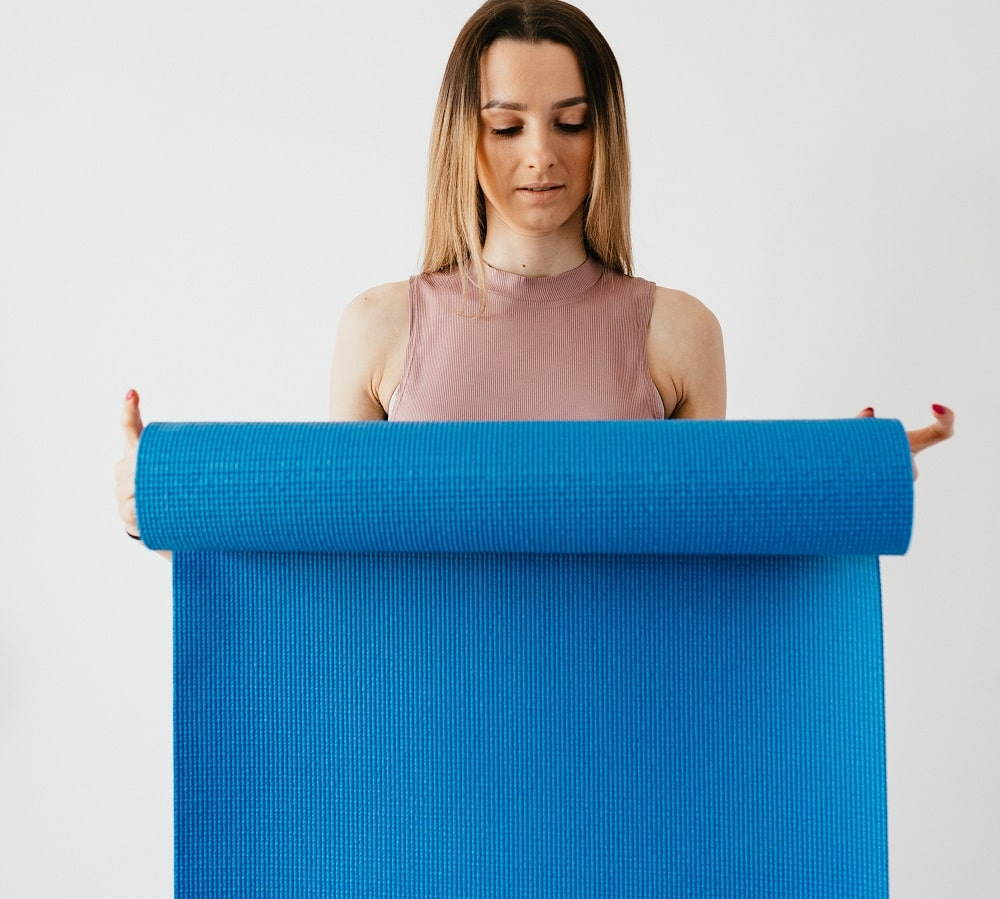 A woman rolling up her blue yoga mat for traveling.