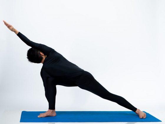 A man doing Parivrtta parsvakonasana (Revolved side angle Pose) yoga.