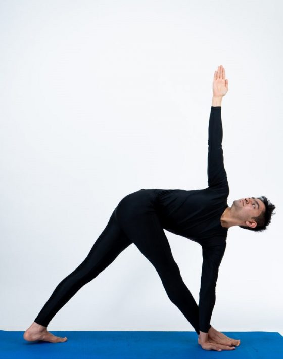 A man doing Parivrtta trikonasana (Revolved Triangle Pose) yoga.