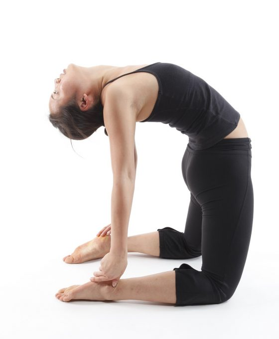 A woman in black isolated in white background doing yoga Camel Pose.