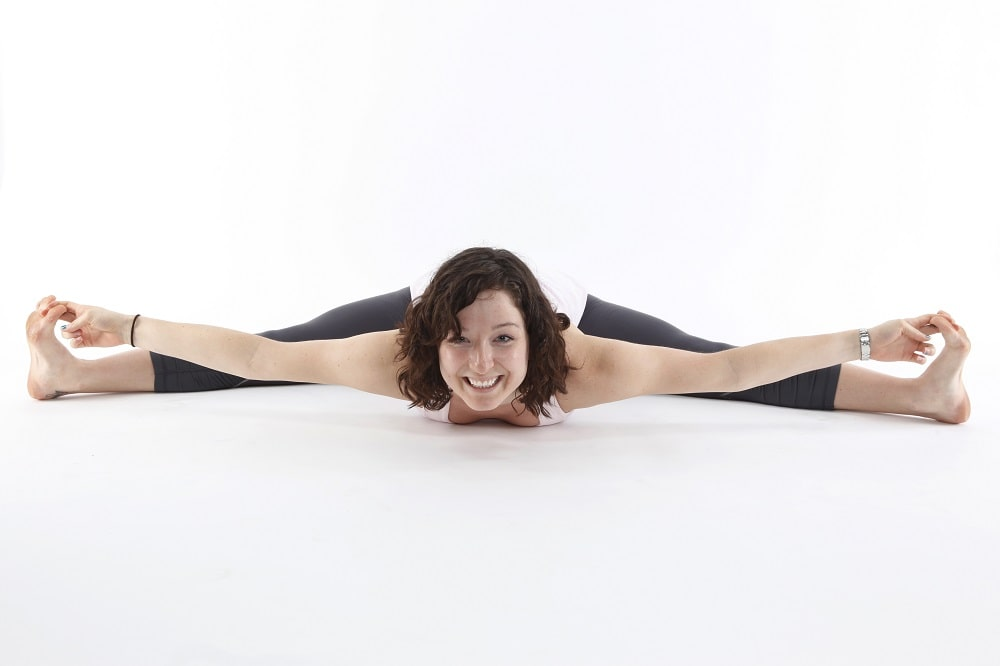 A smiling woman showing flexible hips while doing a full split for her yoga routine.