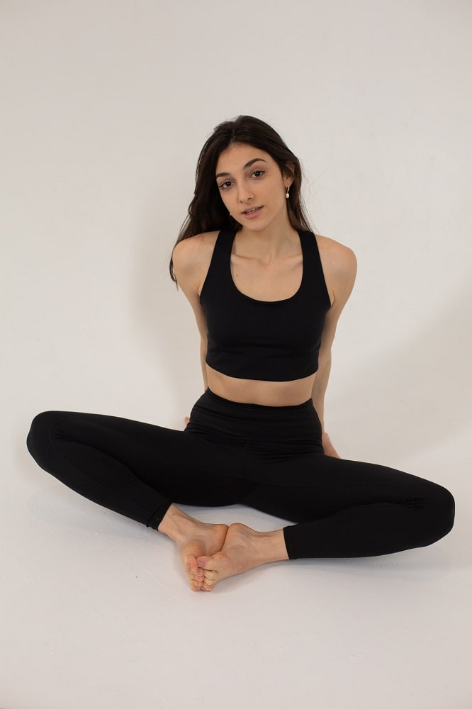 A woman in a black sports top and matching yoga leggings, doing Butterfly Pose or Baddha Konasana as a beginner yoga pose.