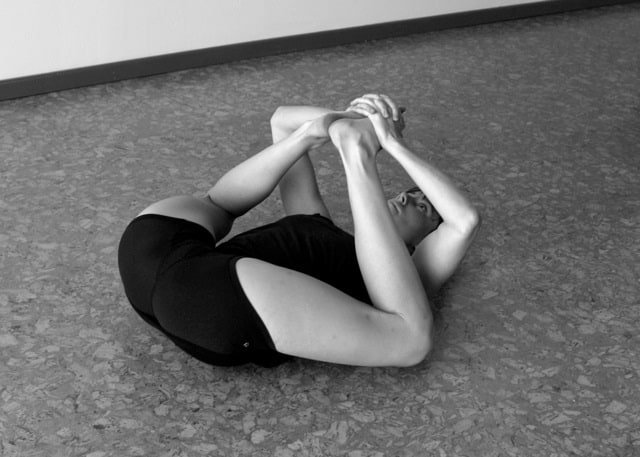A woman doing Happy Baby Pose or Ananda Balasana as a deep hip opener for her yoga routine.