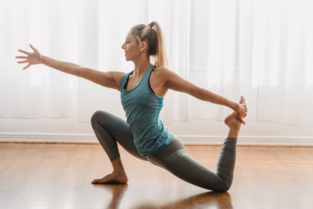 A woman doing Low Lunge Pose or Anjaneyasana as a classic stretch to open up the hip flexors.