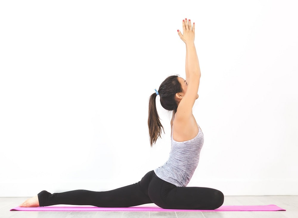 A woman doing Pigeon Pose or Eka Pada Rajakapotasana to improve the external rotation on one hip while stretching the hip flexor of the other.