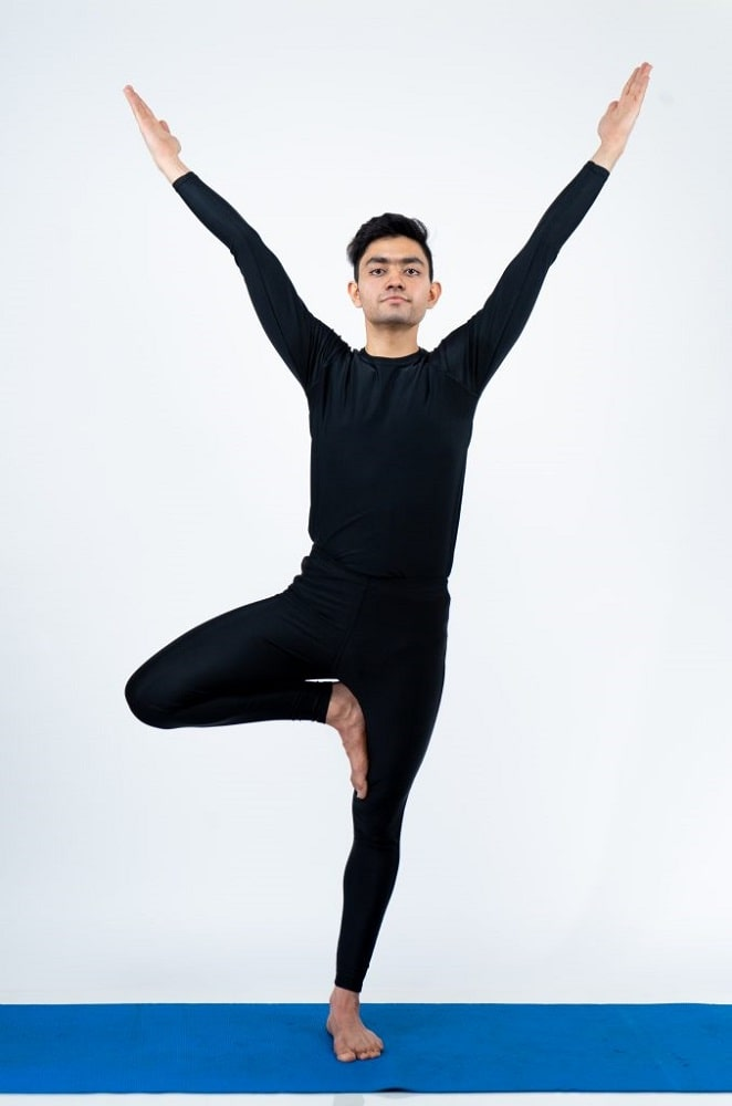 A man wearing a black long-sleeve shirt and pants, doing Tree Pose to warm up and strengthen the leg muscles.