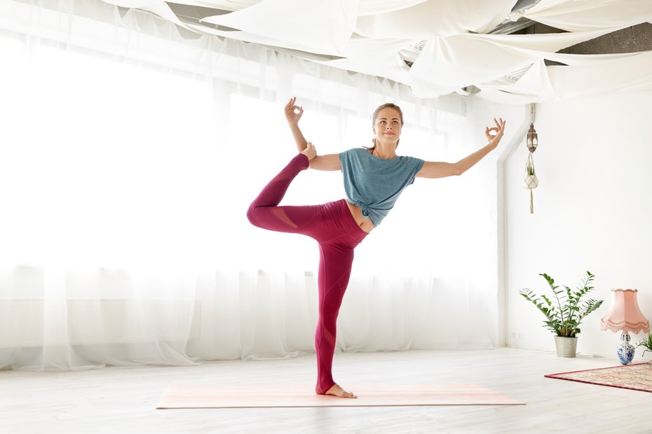 A woman wearing a blue shirt and pink yoga pants, doing a one-legged standing yoga pose to prepare herself for Half Lotus Toe Balance Pose.