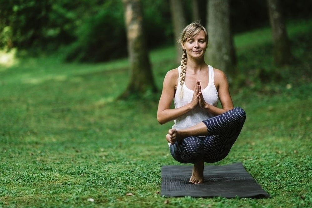 A woman wearing a white sports top and printed yoga pants doing Half Lotus Toe Balance Pose.