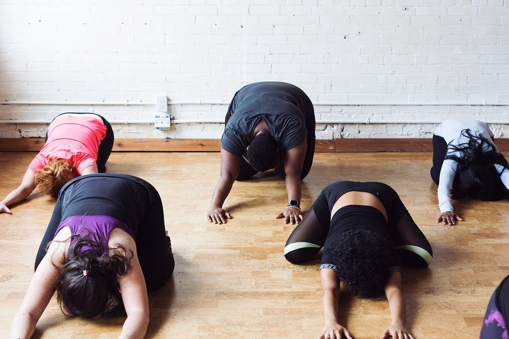 A group of yoga students doing Prone Pose in class, while focusing on their breathing.