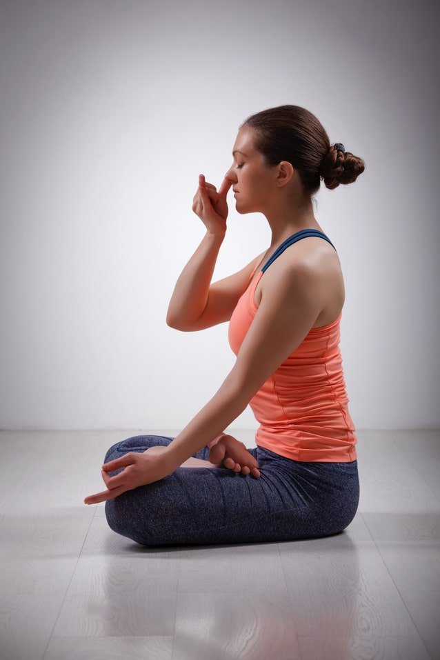 A yoga practitioner using her right hand for mrigi mudra, while practicing her breathing technique to improve clarity and focus.