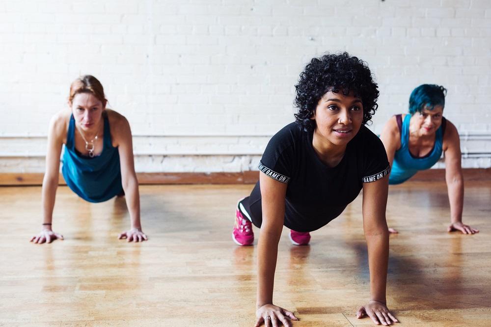 Three fitness women doing plank pose yoga.