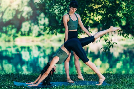 A female yoga instructor assisting her student achieve the proper form during private yoga session outdoors.